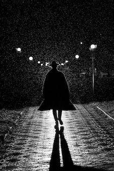 누아르 스타일의 밤 거리에서 비가 내리는 코트와 모자에있는 남성 탐정의 어두운 실루엣