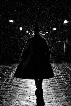 느와르 스타일로 도시의 밤 거리에서 빗속에서 코트와 모자를 쓴 남자의 어두운 실루엣