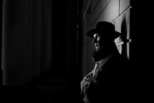 범죄 느와르 스타일로 밤에 그의 얼굴에 모자와 흉터가있는 비옷을 입은 남자의 어두운 실루엣
