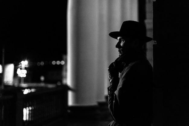 밤에 그의 얼굴에 모자와 흉터가있는 비옷을 입은 남자의 어두운 실루엣