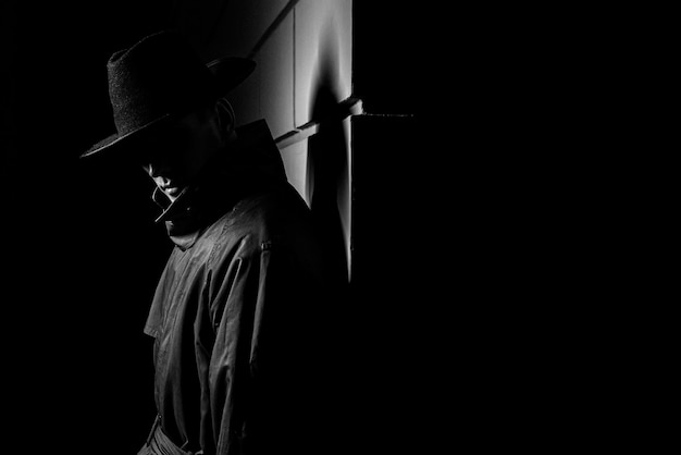범죄 느와르 스타일의 거리에서 밤에 모자와 비옷을 입은 남자의 어두운 실루엣