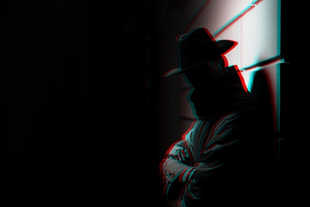夜に帽子をかぶったレインコートを着た男の暗いシルエット