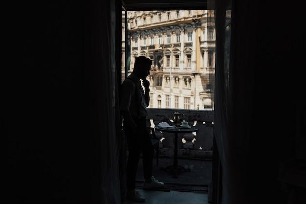 Темный силуэт человека в стильной одежде, глядя на старое здание
