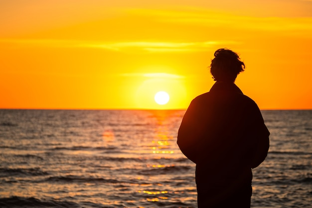 黄金の夕日の海のそばに立っている男の暗いシルエット。夕日を眺める孤独なティーンエイジャー。