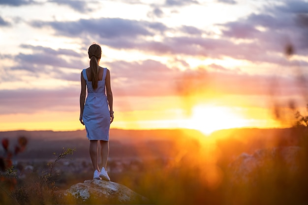 야외에서 석양을 바라보며 서 있는 여름 드레스를 입은 젊은 여성의 어두운 실루엣.