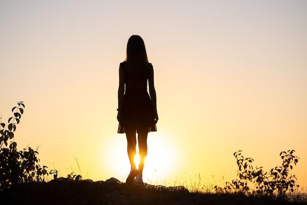 여름에 야외에서 일몰보기를 즐기는 돌에 서있는 젊은 여자의 어두운 실루엣.