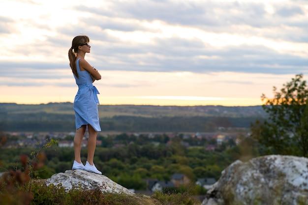 Темный силуэт молодой женщины, стоящей на камне, наслаждаясь видом на закат на открытом воздухе летом.