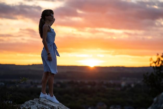 夏の屋外で夕日の景色を楽しむ石の上に立っている若い女性の暗いシルエット。