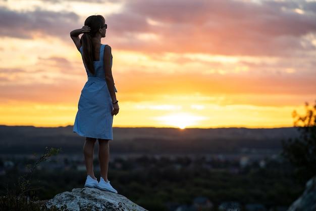야외에서 일몰 자연의보기를 즐기고 서있는 젊은 여자의 어두운 실루엣.