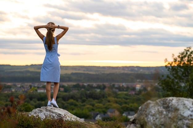 Темный силуэт молодой женщины, стоящей с поднятыми руками на камне, наслаждаясь видом на закат на открытом воздухе летом.
