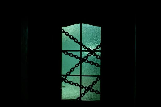 超自然的な緑色の光でチェーン付きのガラスのドアの暗いシルエット。ハロウィーンのドアの後ろの部屋で一人で鎖でロックされています。夜の誘。家の悪。お化け屋敷の中。暗闇の中で一人で。