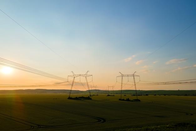 日の出の電力線と高圧塔の暗いシルエット。