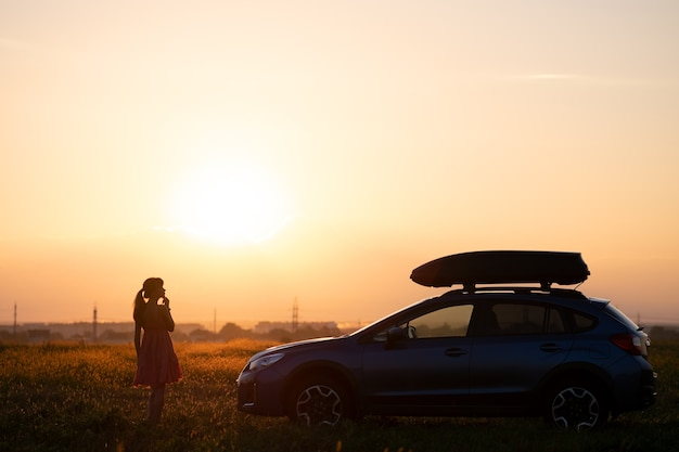 カラフルな日の出の景色を楽しむ芝生の牧草地で彼女の車の近くでリラックスした孤独な女性の暗いシルエット。 suv車の横でロードトリップ中に休んでいる若い女性ドライバー。