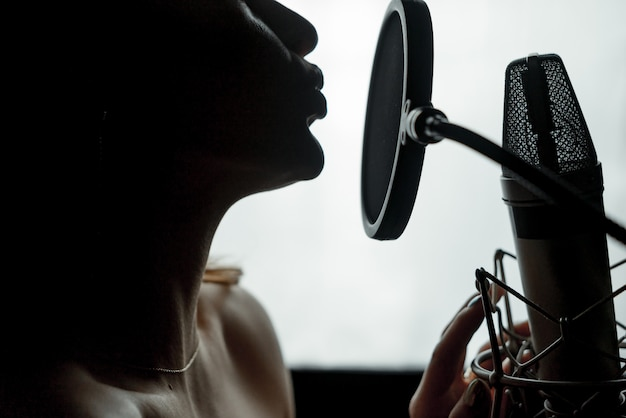 Dark silhouette profile of a young female with bare shoulders singing at the microphone