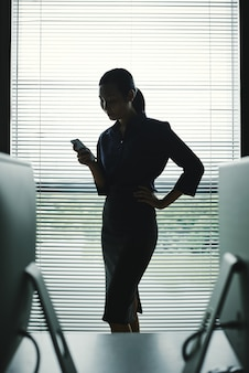 Dark silhouette of woman with smartphone standing in office at window with blinds