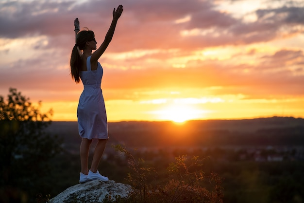 Dark silhouette of a young woman standing with raised up hands on a stone enjoying sunset view outdoors in summer.