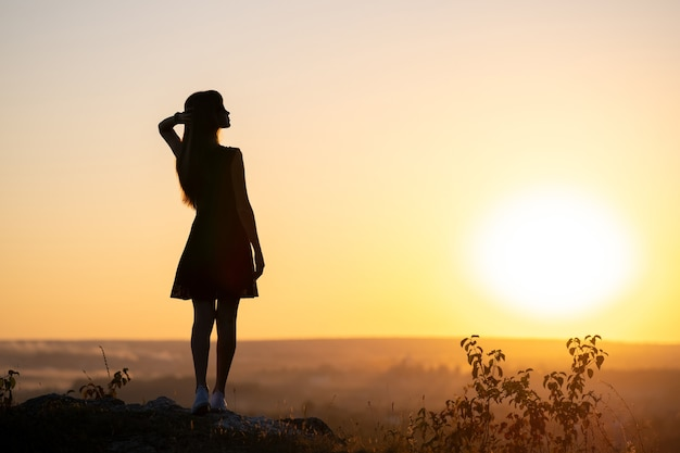 Dark silhouette of a young woman in summer dress standing outdoors enjoying view of nature at sunset.