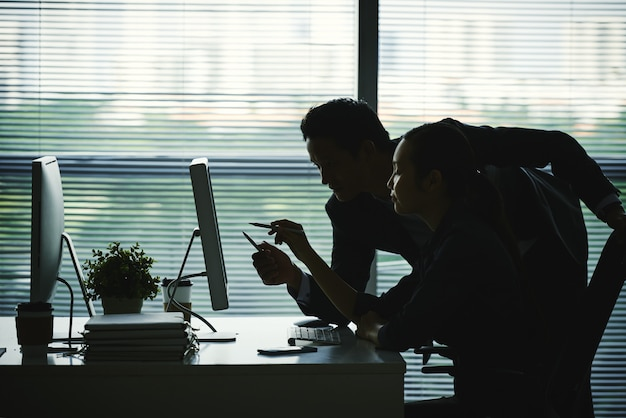 Dark silhouettes of colleagues pointing at computer screen in office against window