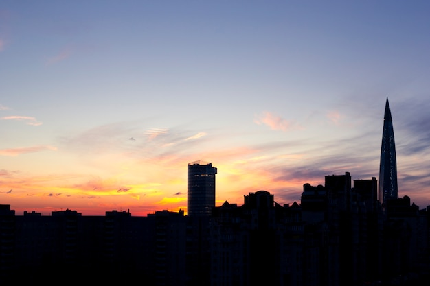 Dark silhouettes of urban buildings, houses and skyscrapers on background of colorful sunset with cirrus clouds