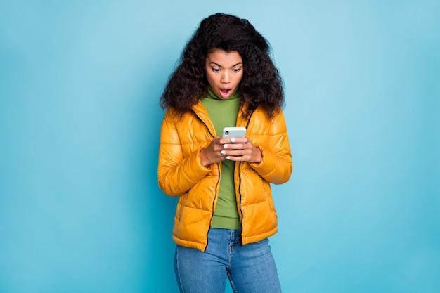 暗い肌の巻き毛の女性が電話の手を握って口を開ける目を信じていない否定的なコメントは黄色のオーバーコートジーンズセーター孤立した青い色の壁を着用