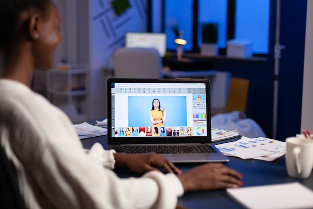 Dark skin freelancer retoucher woman working overtime on laptop with photo editing software