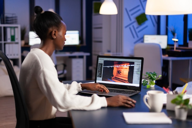 전문 노트북을 사용하여 비즈니스 사무실에서 자정에 비디오 게임에서 일하는 어두운 피부 게이머 개발자