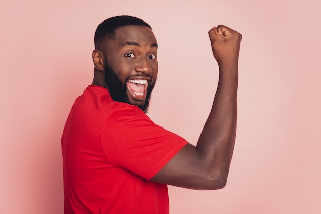 Dark skin guy raise fists victory look empty space isolated over pink background