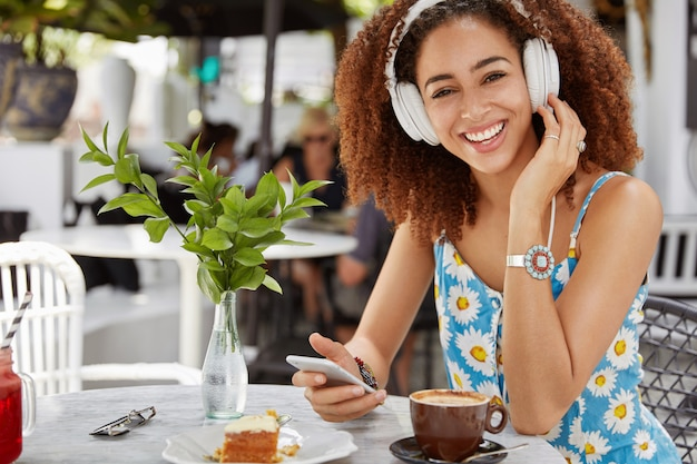 Dark skinned african american woman enjoys perfect sound of favourite song in headphones, connected to cell phone and chooses audio in playlist, drinks coffee in restaurant and eats dessert.