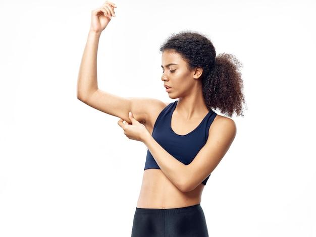 浅黒い肌のアフリカ系アメリカ人女性がトラックスーツでポーズをとって、スポーツをして