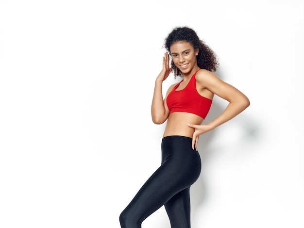 Dark-skinned african american woman posing in a tracksuit and doing sports