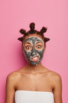 La donna infastidita dalla pelle scura applica una maschera all'argilla contro l'acne sul viso, ringiovanisce la pelle problematica, si trova avvolta in un asciugamano da bagno, ha i panini per capelli, stringe i denti, isolata sul muro rosa cosmetologia