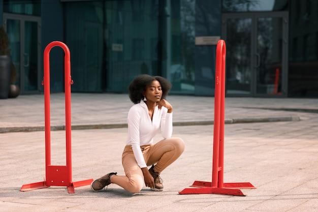 浅黒い肌の魅力的な女性が街に座っています