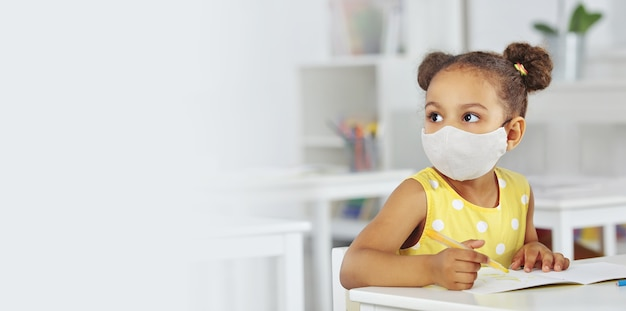 A dark-skinned baby girl in a medical mask for respiratory protection in a yellow dress listens attentively to the teacher.