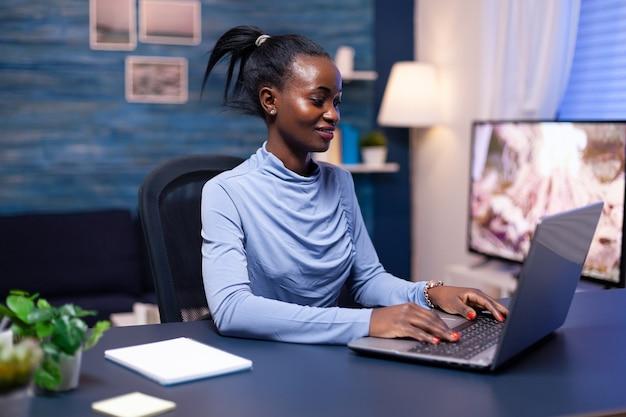 어두운 피부의 비즈니스 여성은 늦은 밤 집에서 노트북 컴퓨터를 사용하여 마감일을 마치기 위해 열심히 일하고 있습니다. 키보드에 쓰는 개인 직장에 앉아 있는 흑인 기업가.
