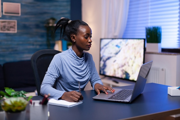 Dark skinned businesswoman working remote from home office late at night using laptop. black entrepreneur sitting in personal workplace writing on keyboard.