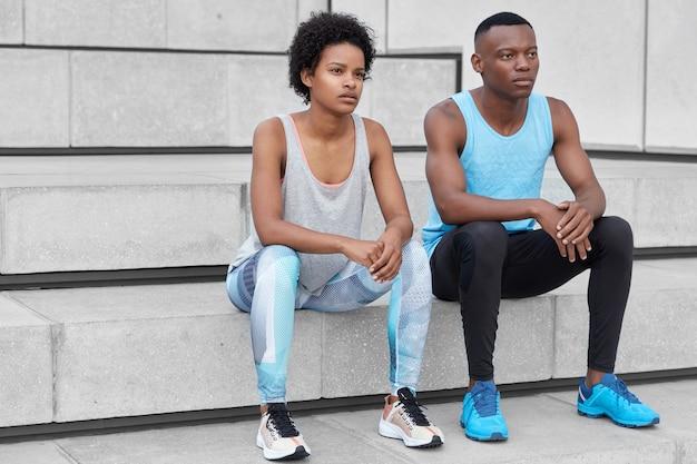 スポーツウェアに身を包んだ浅黒い肌のカップル、快適なトレーナー、有酸素トレーニングの後に休憩を取り、街の階段に座って、距離に集中し、少し疲れています。スポーツが好きなガールフレンドとボーイフレンド