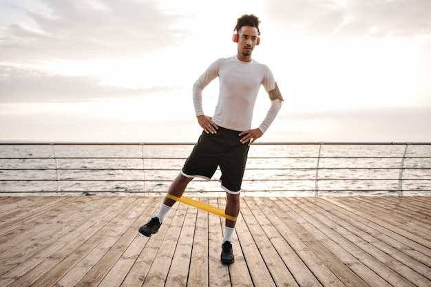 Dark-skinned curly brunette man in white long-sleeved t-shirt and black shorts listens to music in headphones and does exercises with fitness rubber near sea