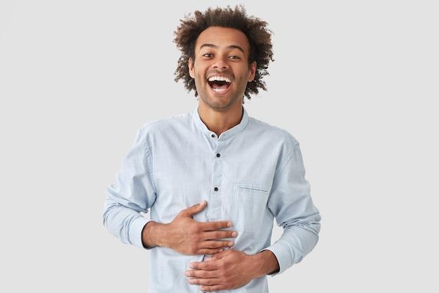 Maschio riccio dalla pelle scura in alto spirito, ridacchia allegramente, sente qualcosa di divertente, vestito con una camicia elegante, posa contro il muro bianco. il giovane afroamericano soddisfatto si sente felicissimo