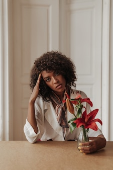 Dark-skinned curly serious woman leans on table, touches face, looks at front and holds vase with red flowers in cozy room