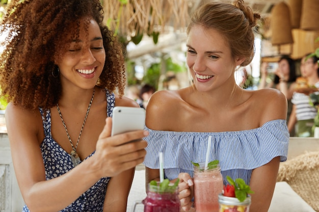 Dark skinned curly woman with positive expression shows photos to her best friend on smart phone, drink smoothie. lesbian couple recreate in restaurant with modern gadget. friendship concept.