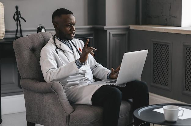 어두운 피부 의사가 노트북을 흔들며 skype 줌에 대한 이야기. 고품질 사진