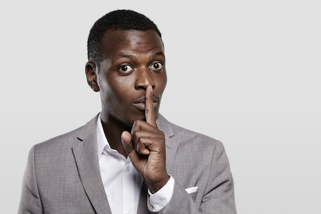Dark-skinned entrepreneur in gray suit holding finger on his lips, asking to keep confidential information private, concealing commercial secret, saying 'hush'.