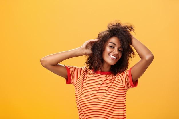 Темнокожая женщина в игривом настроении танцует и улыбается над оранжевой стеной