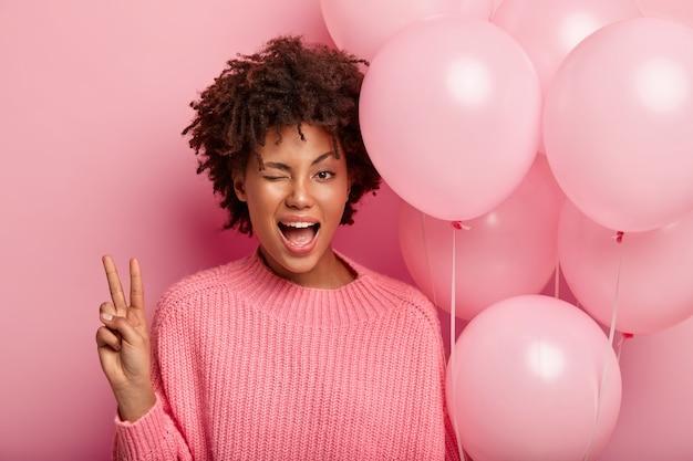 Il modello femminile dalla pelle scura sbatte le palpebre, mostra un gesto di pace, indossa un maglione rosa e trasporta mongolfiere, si diverte nella cerchia dei migliori amici, isolato contro il muro roseo. gioventù, concetto di celebrazione