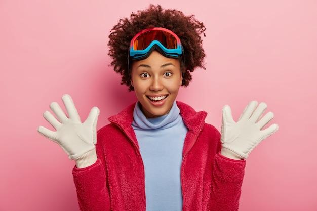 Темнокожая лыжница поднимает ладони в белых перчатках, развлекается после катания на сноуборде, радостно смеется, носит защитную маску, водолазку и красную куртку, отдыхает на розовом фоне.