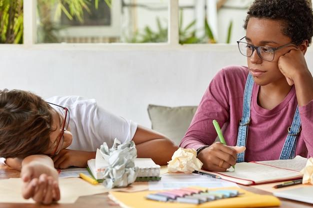 Studentessa dalla pelle scura indossa occhiali trasparenti, guarda seriamente il compagno di classe stanco, lavora insieme al documento del corso, posa alla scrivania con fogli e blocco note, collabora per imparare il materiale.