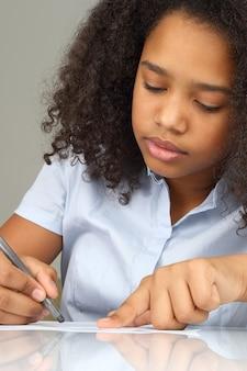 어두운 피부의 소녀가 종이에 연필을 그립니다.
