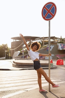 Dark-skinned girl having fun on the street in the summer