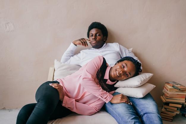 Dark skinned girl lying on her boyfriend legs in studio.