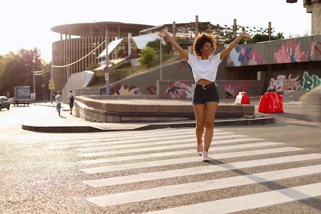 浅黒い肌の女の子が街を歩いて楽しんでいます